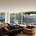 Dug out terrace and stone clad retaining wall act as the fourth wall of the living room through full height windows